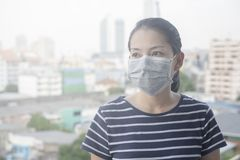 A máscara protetora vestindo da mulher de N95 devido à poluição do ar na cidade tem as partículas ou o PM 2 5 com construção da c imagem de stock