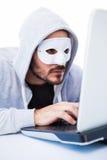 Máscara que lleva del hombre mientras que corta en el ordenador portátil Fotografía de archivo libre de regalías