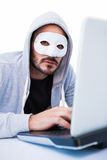 Máscara que lleva del hombre mientras que corta en el ordenador portátil Fotos de archivo libres de regalías