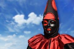 Máscara roja del carnaval del pierrot, con el fondo del cielo y las nubes, Venecia, Italia Imágenes de archivo libres de regalías