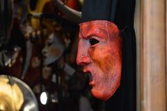 Máscara veneciana roja sobre el guardapolvo flojo negro fotos de archivo libres de regalías