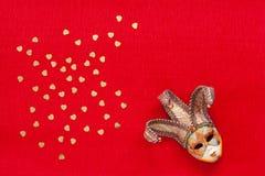 Máscara Venetian com confetes do brilho do ouro da forma do coração A vista superior, fecha-se acima no fundo vermelho fotos de stock