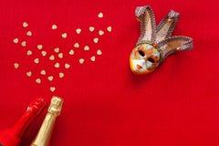 Máscara Venetian e duas garrafas do champanhe com confetes do brilho do ouro da forma do coração A vista superior, fecha-se acima imagens de stock royalty free