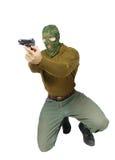 A máscara vestindo da camuflagem do homem está apontando com uma pistola Foto de Stock
