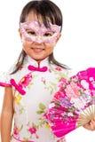 Máscara vestindo da menina chinesa pequena asiática e guardar o fã oriental Fotos de Stock Royalty Free