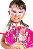 Máscara vestindo da menina chinesa pequena asiática e guardar o fã oriental Foto de Stock