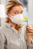 Máscara vestindo da mulher na cara que tem a alergia às flores imagens de stock
