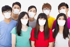 Máscara vestindo do grupo de estudantes novo fotografia de stock