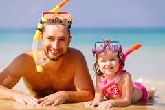 Máscara vestindo feliz do pai e da criança da família e riso no beac fotografia de stock