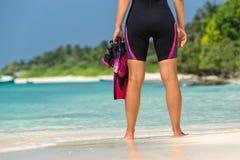 Máscara y aletas de la tenencia de la mujer para nadar en la playa tropical Fotografía de archivo