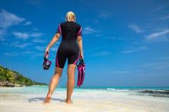 Máscara y aletas de la tenencia de la mujer para nadar en la playa tropical Imagenes de archivo