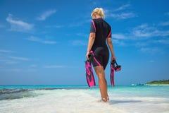Máscara y aletas de la tenencia de la mujer para nadar en la playa tropical Fotos de archivo