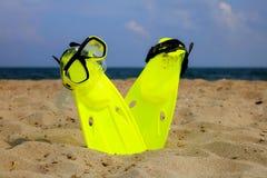 Máscara y aletas que bucean en la playa arenosa foto de archivo