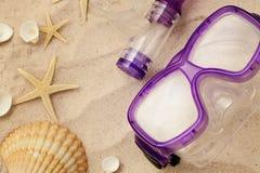 Máscara y conchas marinas que se zambullen en la playa de la arena Foto de archivo