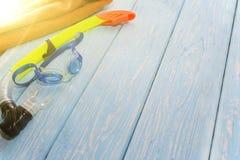 Máscara y tubo respirador que se zambullen de los vidrios en fondo azul de madera Foto de archivo