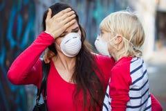 Máscaraes protetoras vestindo da mulher e do filho Imagem de Stock Royalty Free