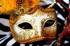 Máscaras brillantes de la mascarada en silla retra Fotografía de archivo