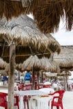 Máscaras de Palapa na praia com tabelas e as cadeiras plásticas sob elas - focalize no primeiro plano com fundo borrado com unide imagens de stock royalty free