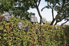 Máscaras en las barras de hierro para la decoración del jardín Imagenes de archivo