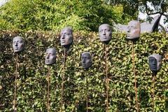 Máscaras en las barras de hierro para la decoración del jardín Fotografía de archivo libre de regalías