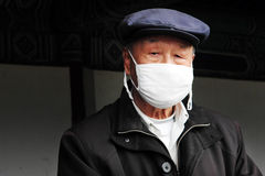 Máscaras quirúrgicas chinas del desgaste de hombre Foto de archivo