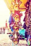 Máscaras venecianas hermosas con la iglesia de San Giorgio Maggiore en el fondo Tienda de la calle en Venecia Italia al aire libr imagenes de archivo