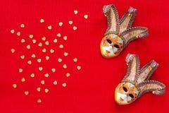 Máscaras Venetian com confetes do brilho do ouro da forma do coração A vista superior, fecha-se acima no fundo vermelho fotografia de stock