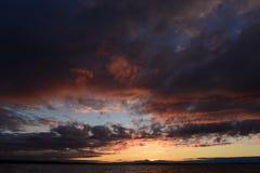 Máscaras vermelhas da luz solar em um céu nebuloso sombrio no por do sol Imagem de Stock Royalty Free