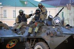 Máscaras vestindo e capacetes do pelotão armado do motim que sentam-se na tropa Imagens de Stock Royalty Free