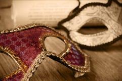 Máscaras y rollo en una superficie de madera en el tono de la sepia Foto de archivo libre de regalías