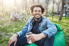 Mâle à la peau foncée émotif avec la coiffure Afro, se reposant sur la chaise en parc tout en parlant à quelqu'un et au café pota Photos stock