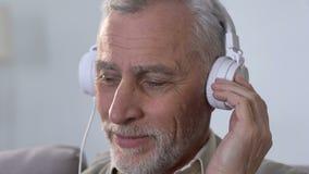 Mâle âgé dans des écouteurs écoutant la musique, se déplaçant le rythme, style moderne banque de vidéos