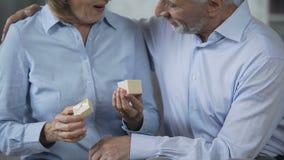 Mâle âgé donnant la petite boîte actuelle à la femelle, femme l'ouvrant et embrassant l'homme banque de vidéos