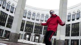 Mâle actif dans des coups secs et durs rouges d'équipement et de lunettes de soleil de sport à côté des colonnes de granit clips vidéos