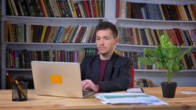 Mâle adulte attirant travaillant sur un ordinateur portable se reposant dans la bibliothèque à l'intérieur sur le fond banque de vidéos