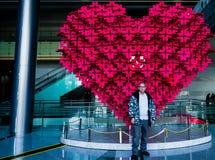 Mâle adulte dans le manteau d'hiver se tenant devant la sculpture en coeur Photo stock