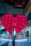 Mâle adulte dans le manteau d'hiver se tenant devant la sculpture en coeur Image stock