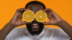 Mâle africain espiègle tenant les yeux avant de tranches oranges, nutrition de vitamine, santé banque de vidéos
