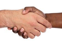 Mâle africain et caucasien se serrant la main Images stock