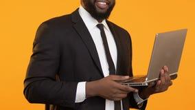 Mâle afro-américain futé travaillant sur l'ordinateur portable et montrant des pouces vers le haut de geste clips vidéos