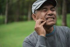 Mâle asiatique supérieur ayant le mal de dents image libre de droits
