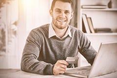 Mâle avec la carte de crédit à son ordinateur portable Images stock