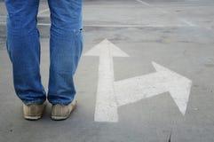 Mâle avec les jeans et la flèche blanche de direction Photographie stock