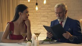 Mâle avide choqué avec des prix élevés dans la facture de luxe de restaurant, dîner romantique banque de vidéos