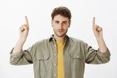Mâle barbu beau avec les cheveux courts bouclés dans la chemise au-dessus du T-shirt jaune, soulevant des index et se dirigeant,  Image libre de droits