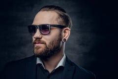 Mâle barbu dans des lunettes de soleil au-dessus de fond gris-foncé image libre de droits
