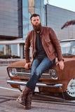 Mâle barbu habillé dans la veste en cuir brune et bottes se penchant sur la rétro voiture accordée dans la ville se garant près d image libre de droits