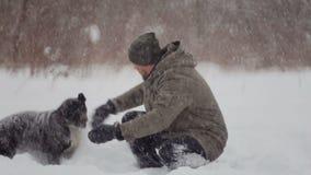 Mâle barbu marchant son animal familier dans les chutes de neige clips vidéos
