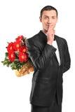 Mâle beau cachant un bouquet des fleurs Photographie stock