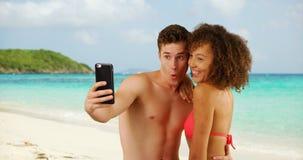 Mâle caucasien beau avec l'ami féminin prenant le selfie sur la plage Image stock